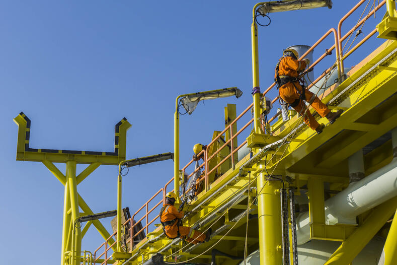 Oil workers using fall protection