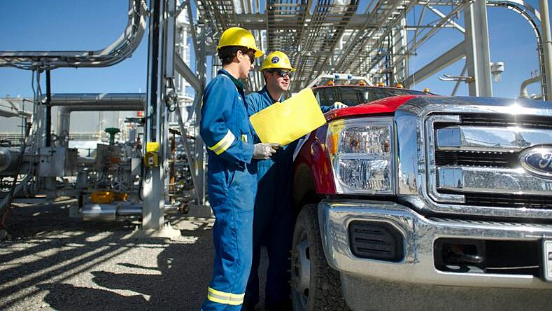 Two oil workers in coveralls talking