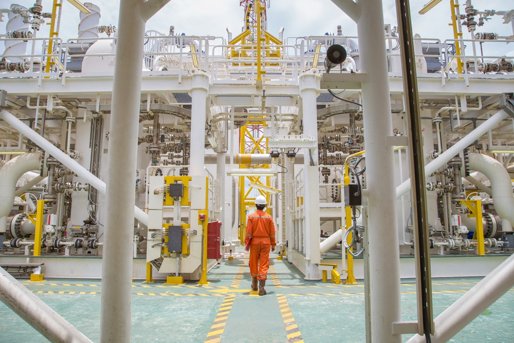 Oil worker inspecting oil rig