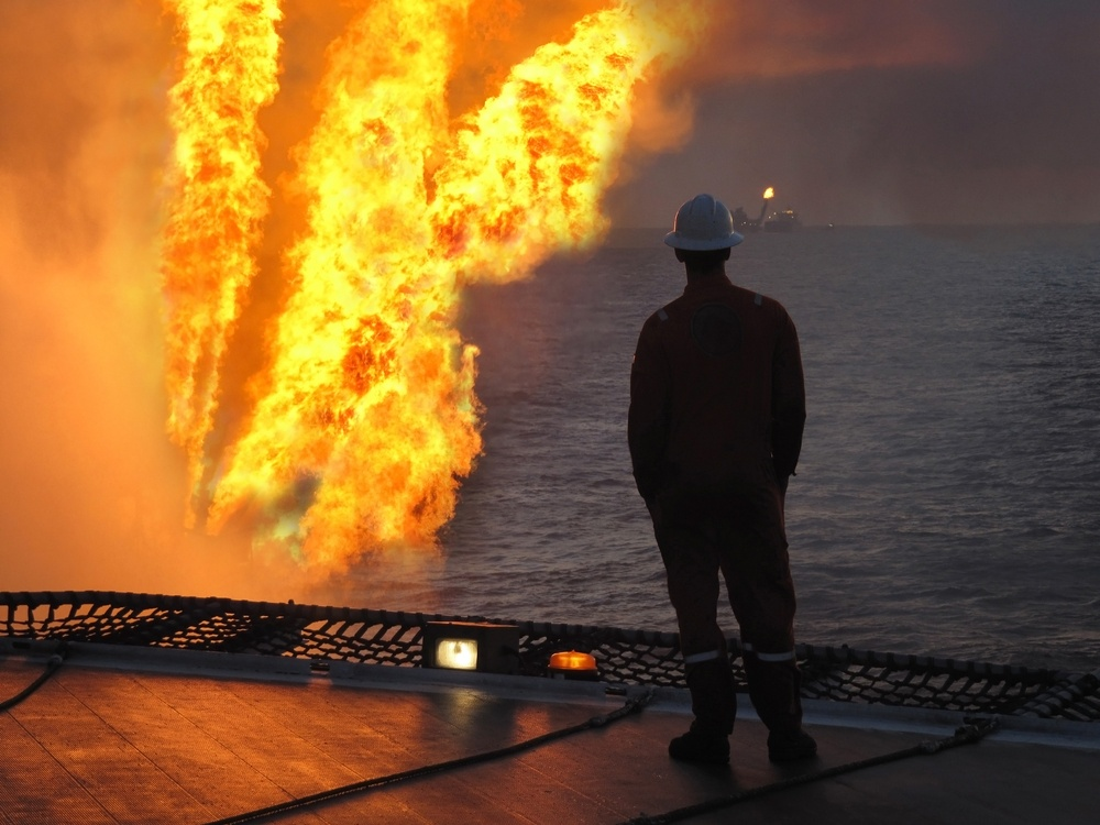 Oil worker standing next to fire on oil rig